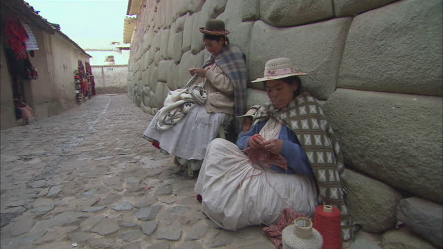 ws two peruvian women sitting against stone wall in village and knitting / cuzco region, peru - stone wall stock videos and b-roll footage