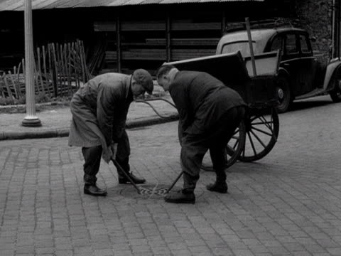 two pest controllers place rat poison into a london sewer. 1955. - wirbeltier stock-videos und b-roll-filmmaterial
