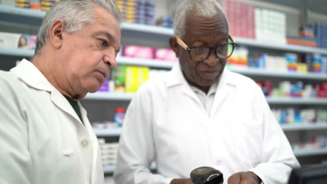 two pharmacists working in a drugstore - computer part stock videos and b-roll footage