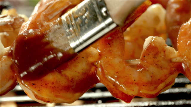 ecu two pieces of shrimp being grilled as basting brush swipes bbq sauce over shrimp - bbq brush stock videos and b-roll footage