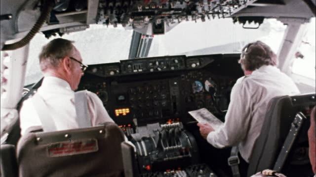 Two pilots and navigator perform a pre-flight check in the cockpit of an airliner while the ground crew loads the plane and a air traffic controller monitors the radar screen in the control tower.