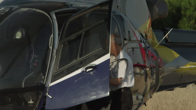 LS PAN CU two pilots approaching and boarding business helicopter, RED R3D 4K
