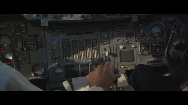 CU, Two pilots in jet cockpit, close-up of hands and control panel