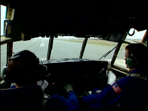 cu pan two pilots in us coast guard c-130 hercules cockpit, riding on runway, international ice patrol over atlantic ocean, st john's, newfoundland, canada - 飛行士点の映像素材/bロール