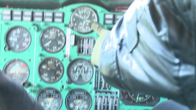 Two pilots press controls and buttons inside a helicopter cockpit. Available in HD.