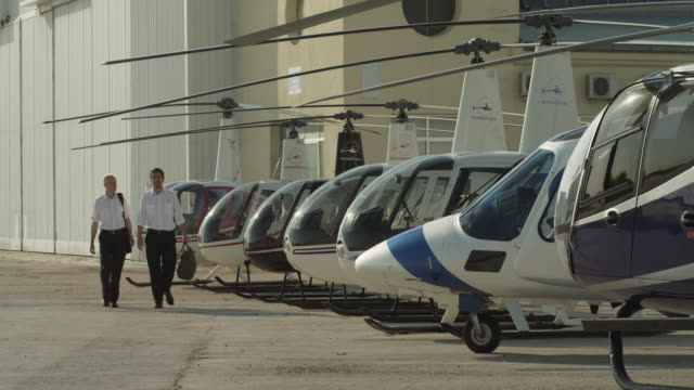 LS  two pilots walking to camera along helicopter flight line in front of hangars, approach and board business helicopter, RED R3D 4K