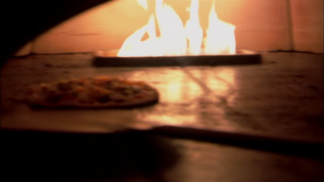 ms, pan, two pizzas being placed in wood fire pizza oven - pizza oven stock videos and b-roll footage