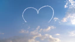 Two planes drawing a heart in the sky with smoke