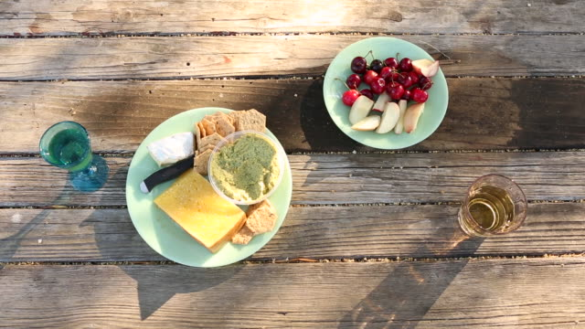 two plates with fruit, cheese, crackers and hummus next to two glasses of white wine. - picnic table stock videos & royalty-free footage