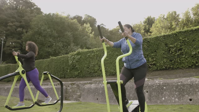 two plus size females exercising at outdoors gym in park, obese black women sports training body positive fitness - gym stock videos & royalty-free footage