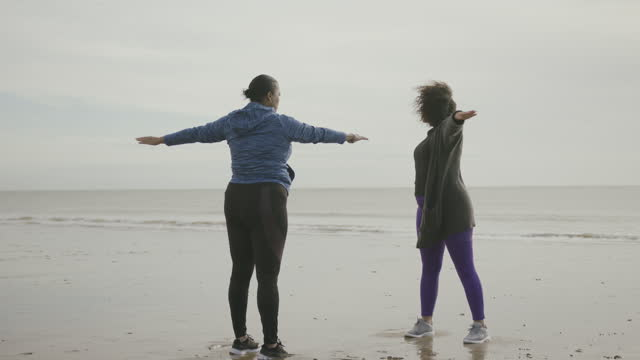 vídeos y material grabado en eventos de stock de two plus size females exercising stretching outdoors on beach, obese black women sports training body positive - equilibrio vida trabajo