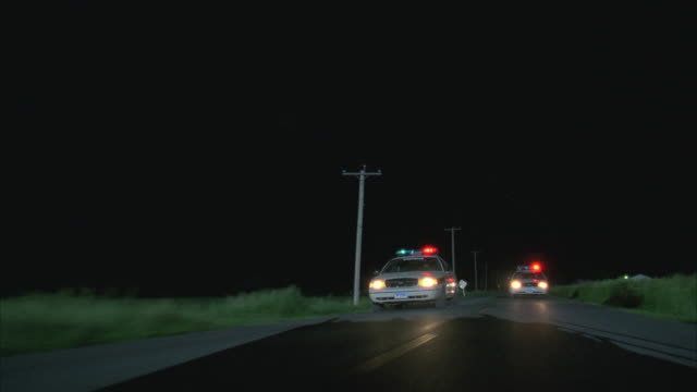 REAR POV Two police cars driving on rural road at night / New York, USA