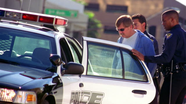 Two police officers assist a man in the back of a police car.