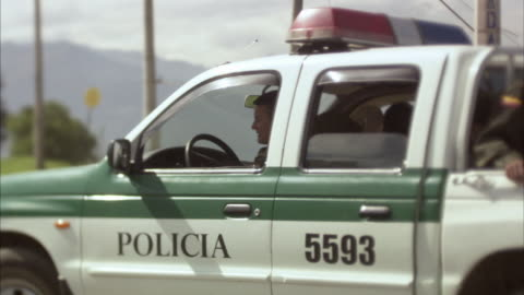 ms two police officers driving, stopping, and exiting police car / bogota, colombia - colombia stock videos & royalty-free footage