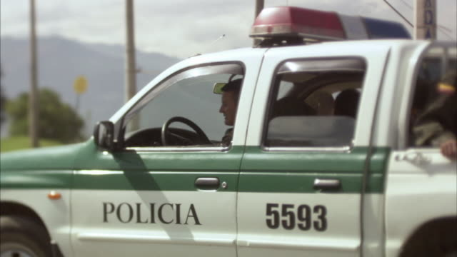 ms two police officers driving, stopping, and exiting police car / bogota, colombia - colombia stock videos and b-roll footage