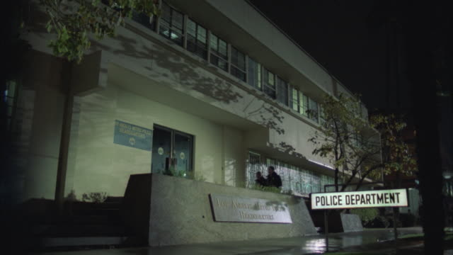 ms, two police officers entering and leaving los angeles metro police station at night, los angeles, california, usa - 警察点の映像素材/bロール