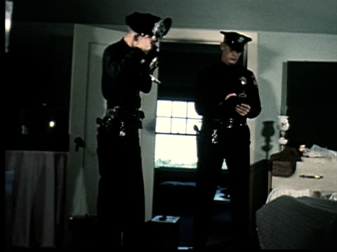 1965 ms two police officers investigating crime scene in bedroom/ one officer taking notes while other takes photograph with flash/ oakland, california/ audio - oakland california stock videos & royalty-free footage