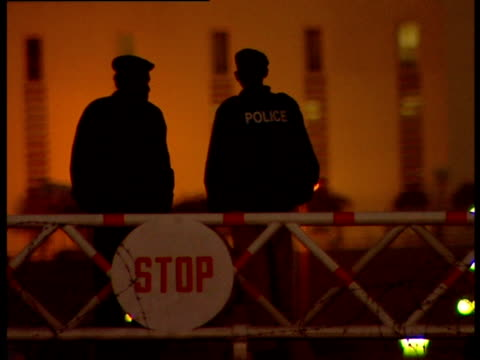 Two police officers leaning on barricade with stop sign