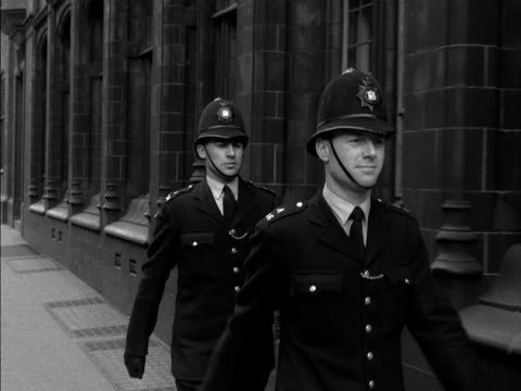 two police officers march along a street before splitting up the camera then follows the lead policeman as he starts his beat along a road 1957 - marching stock videos & royalty-free footage