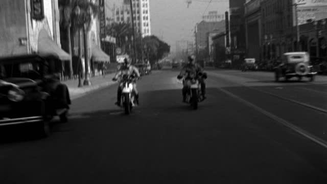 two police officers on motorcycles speed down highland avenue onto hollywood boulevard in hollywood, california. - 1933 stock videos & royalty-free footage