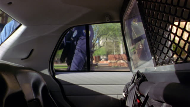 Two police officers put a handcuffed suspect into a police car.