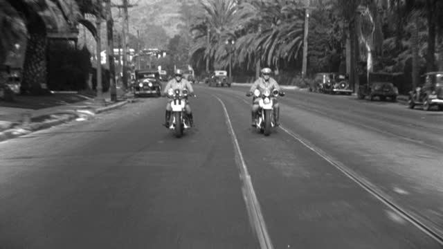 two police officers ride motorcycles down highland avenue to hollywood boulevard in hollywood, california. - 1933 stock videos & royalty-free footage