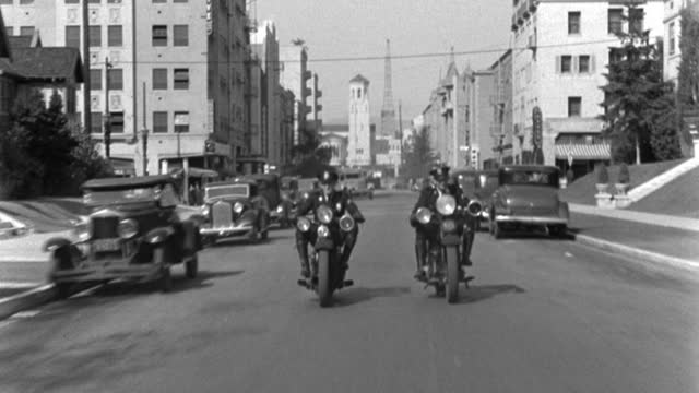 two police officers ride motorcycles side-by-side through a residential district. - 1935 stock videos & royalty-free footage