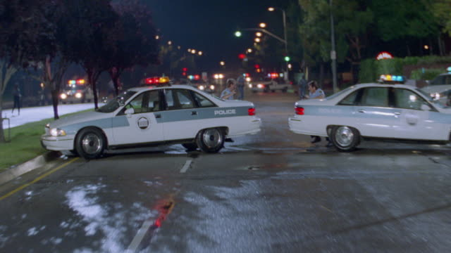 two police officers run away from two police cars parked in a roadblock. - anno 1994 video stock e b–roll