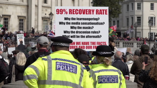 """two police officers stand behind a protestor holding a placard that makes the claim of a """"99 percent recovery rate"""" at a coronavirus conspiracy... - トラファルガー広場点の映像素材/bロール"""