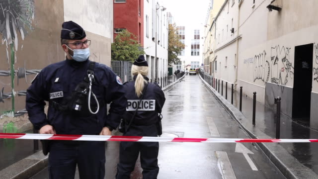 two police officers stand guard at a site after a knife attack near the former headquarters of satirical magazine charlie hebdo in paris, france on... - satira video stock e b–roll
