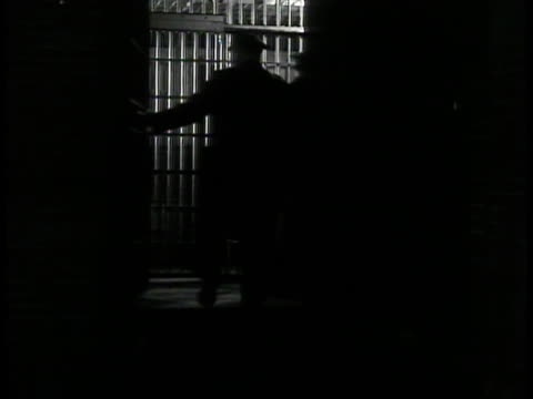 two policemen walking in jail shadows w/ arrested man closing section door. ext street scene w/ two policeman officers standing talking. vs crowded... - new york city 1930s stock videos & royalty-free footage