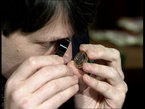 vídeos y material grabado en eventos de stock de two pound coin; tx 27.10.94 itn intwales: royal mint tcms man examining two pound coin with eyeglass zoom in  tx 8.12.95/nat - royal mint