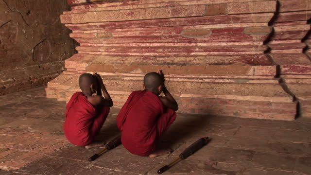 two praying novice monks with buddha hdv163 - adolescence stock videos & royalty-free footage