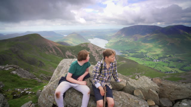 two pre teenage boys at the summit of high stile in the western fells, lake district, cumbria, uk - part of a series stock-videos und b-roll-filmmaterial