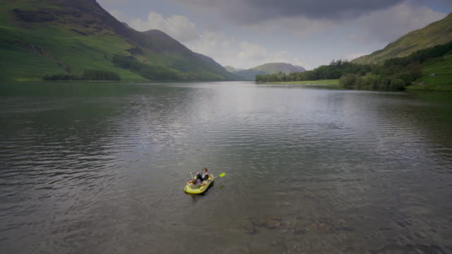 two pre teenage boys with their dingy on the buttermere lake, cumbria, uk - dinghy stock videos & royalty-free footage