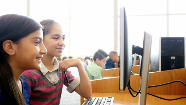vídeos y material grabado en eventos de stock de dos antes de teen medio school estudiantes mujeres trabajar en proyectos en la biblioteca de la escuela madre o laboratorio de computación - niño pre escolar