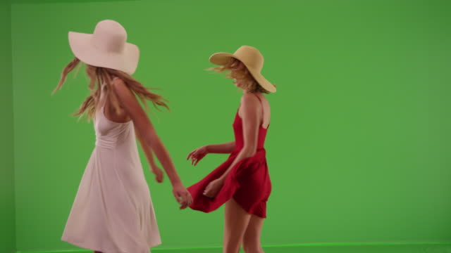 vidéos et rushes de two pretty girlfriends twirling dresses for green chroma key compositing - robe