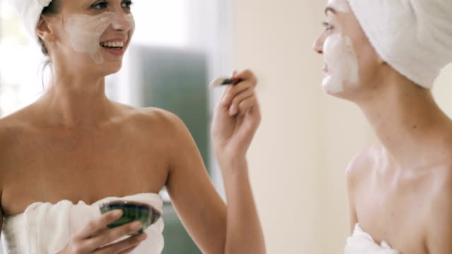 vídeos de stock e filmes b-roll de two pretty women applying a facial mask - spa