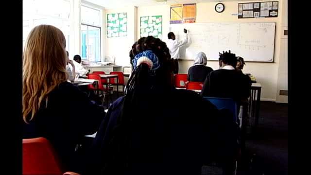 Two primary schools have SATS results annulled Class of schoolchildren writing during lesson