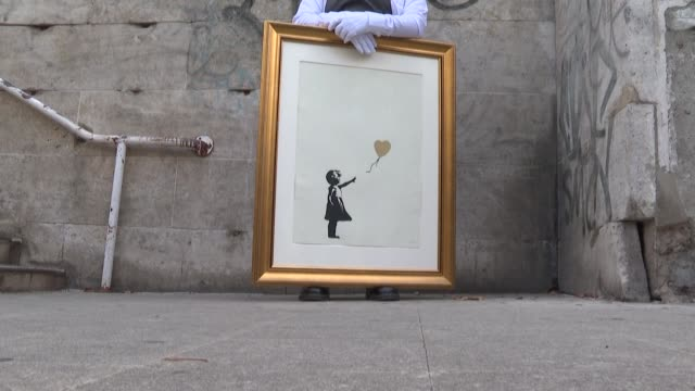 two proofs of banksy's famous artwork girl with balloon originally sprayed in london's south bank in 2002 are shown close to their original location... - auction stock videos & royalty-free footage