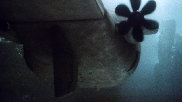 two propellers spin on a nuclear submarine in the ocean. - elica parte di macchina video stock e b–roll