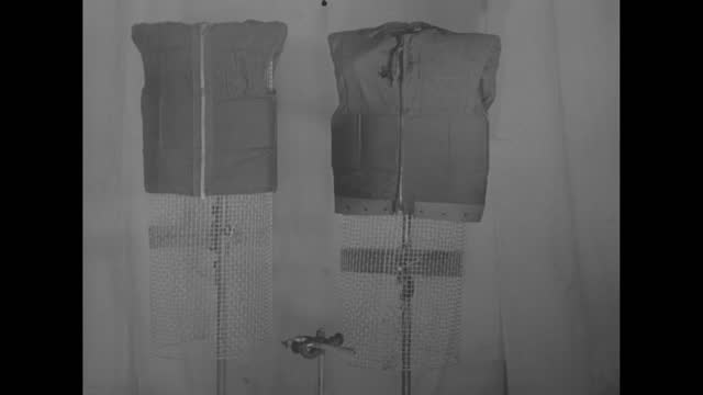 """vidéos et rushes de two protective clothing on poles with chicken wire with the grenade and chicken wire beneath / clapperboard: """"us naval photographic center 2/26/52"""" /... - clap de cinéma"""