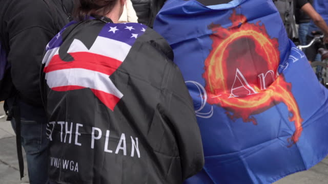 two protestors wear far right cult qanon flags arounds their shoulders as thousands of people gather on trafalgar square for a coronavirus conspiracy... - march month stock videos & royalty-free footage