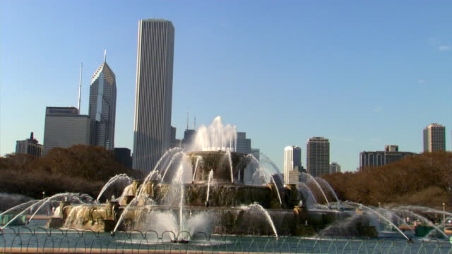 two prudential plaza and the aon center rise behind buckingham fountain in chicago, illinois. - two prudential plaza stock videos & royalty-free footage