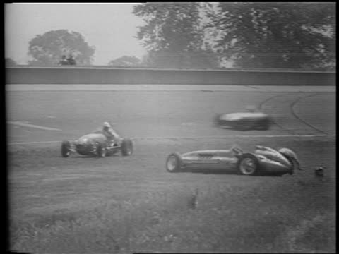 b/w 1953 two race cars parked in grass / one driver falls to ground / cars racing on track in background - 1953 stock videos and b-roll footage