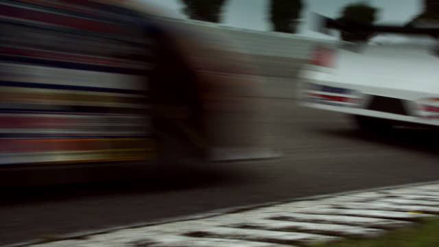 ws pan two racecars driving around curve on racetrack past camera / long pond, pennsylvania, usa - スウィッシュパン点の映像素材/bロール