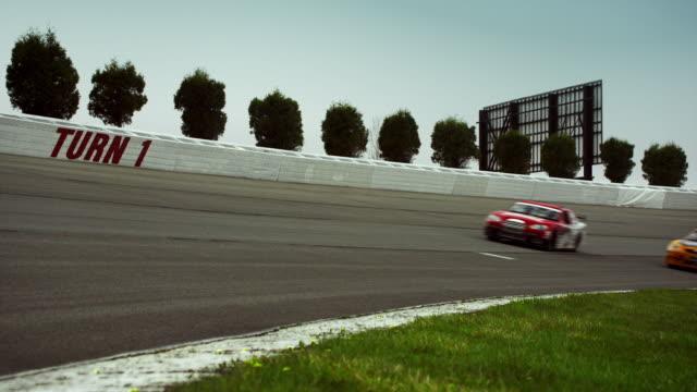 ws two racecars driving on racetrack past camera / long pond, pennsylvania, usa - automobile da corsa video stock e b–roll