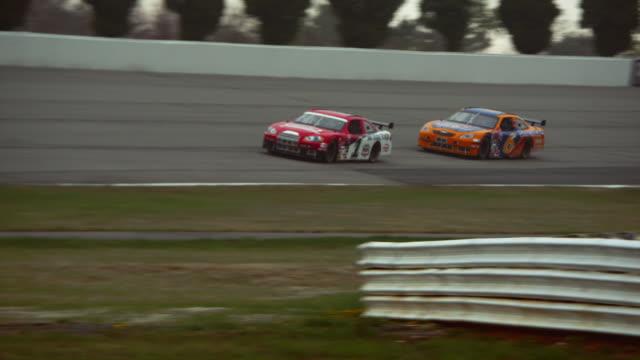 ws pan two racecars driving on racetrack past camera / long pond, pennsylvania, usa - 曲線点の映像素材/bロール
