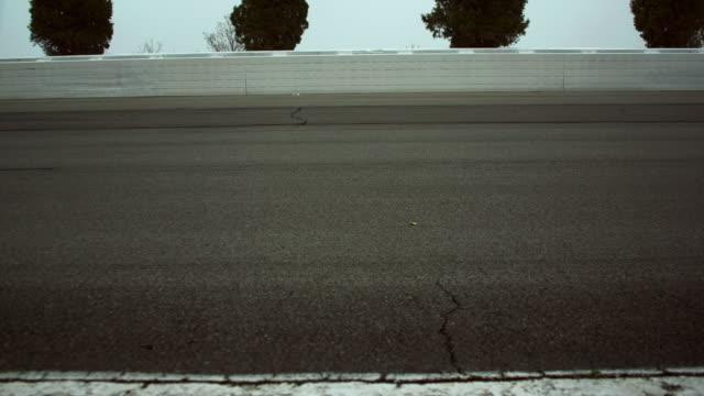 ms pan ws two racecars driving quickly past camera / long pond, pennsylvania, usa - スウィッシュパン点の映像素材/bロール
