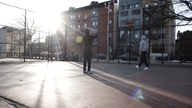 Two racially diverse, young men, in their twenties play basketball at a neighborhood court in Brooklyn, NYC - 4k